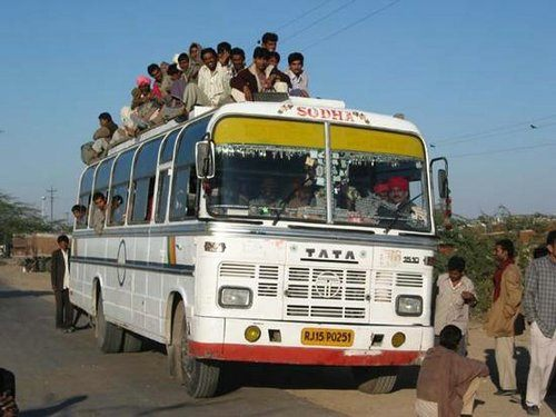 piucture of an indian tata bus with people on the seats in the aisle and on the roof